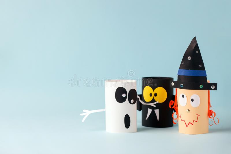 Paper toy ghost, bat, witch for Halloween party. Easy crafts for kids on blue background, copy space, die creative idea from royalty free stock photo