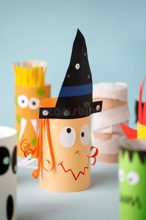 Paper toy witch for Halloween party. Easy crafts for kids on blue background, copy space, die creative idea from toilet tube, royalty free stock photos