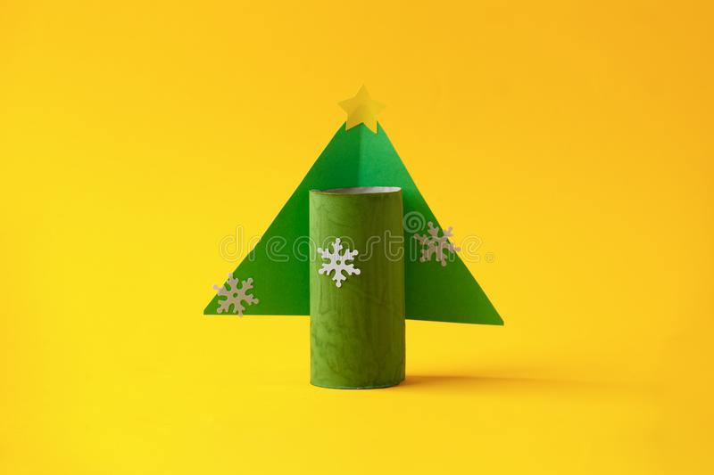 Paper toy xmas tree for Happy new year Merry Christmas party. Easy crafts for kids on yellow background, simple diy idea from stock images