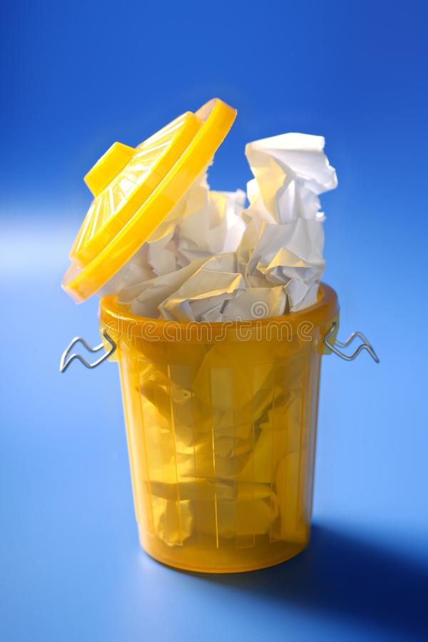 Paper trash in yellow over blue background royalty free stock photography