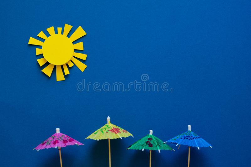 Paper umbrellas under sun. Origami. Sun protection and summer vacation concept.  royalty free stock photo