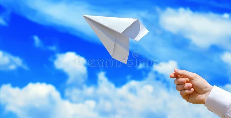 Paper white airplane in the male hand. Airplane against the blue sky royalty free stock photography