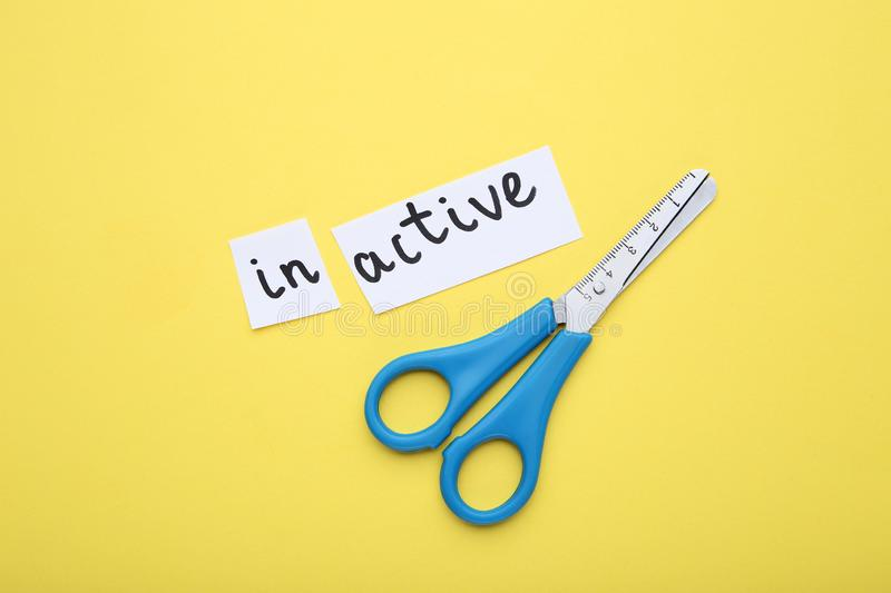 Paper with word Inactive. And scissors on yellow background royalty free stock photography