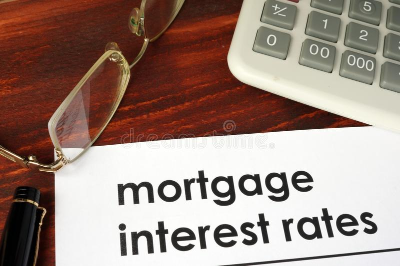Paper with words mortgage interest rates. Paper with words mortgage interest rates on a wooden background stock images