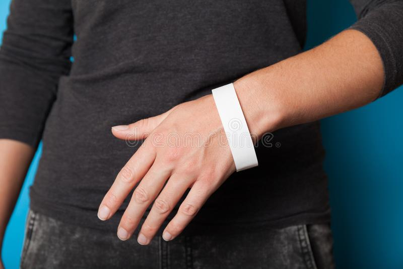 Paper wristband mockup, event bracelet on hand. Empty ticket wrist band design stock photography