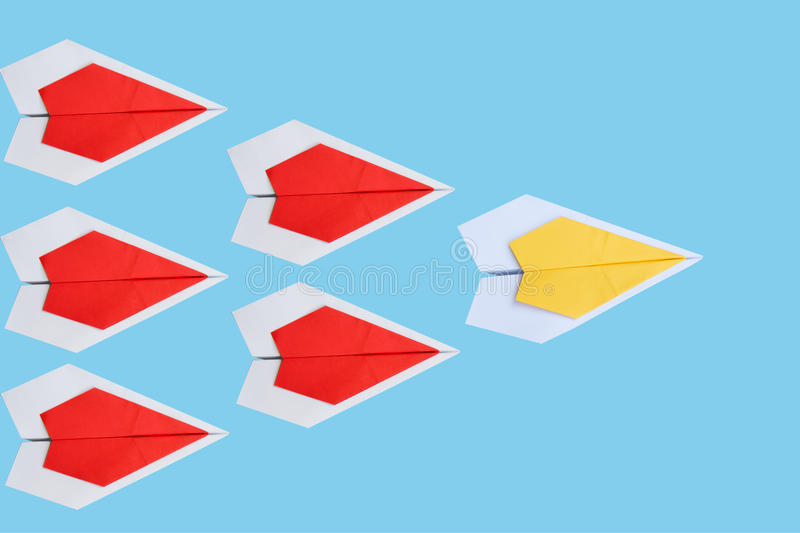 paper yellow airplane as a leader among red airplane , leadership, teamwork royalty free stock images