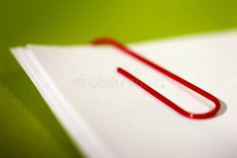 Paperclip. Macro picture of attachment paper by a red paperclip stock photo