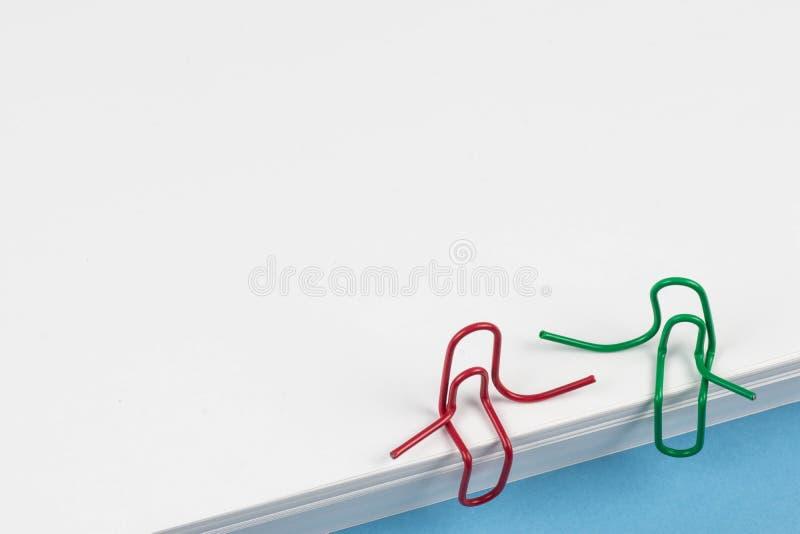Paperclippen rode en groene zitting op een Witboekriem en het spreken van of het hebben van een gesprek Een foto met een exemplaa royalty-vrije stock fotografie