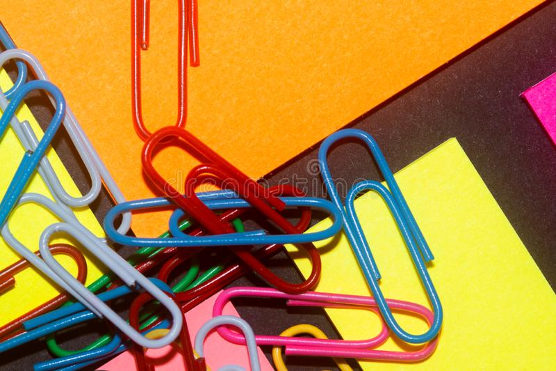 Paperclips on colorful different colour office stickers on black paper. stock photo