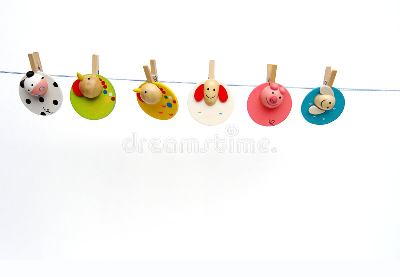 Paperclips on washing line. Clothes pegs on a laundry line - A cute and colourful concept image of six fun and bright wooden paper clips, with cute design, made stock photography