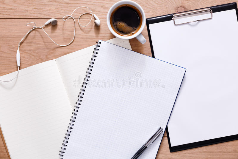 Papers, notepad and coffee on wood background. Notepad, diary, earphones and espresso coffee. Office or student`s devices on modern wooden desk. Working table royalty free stock image