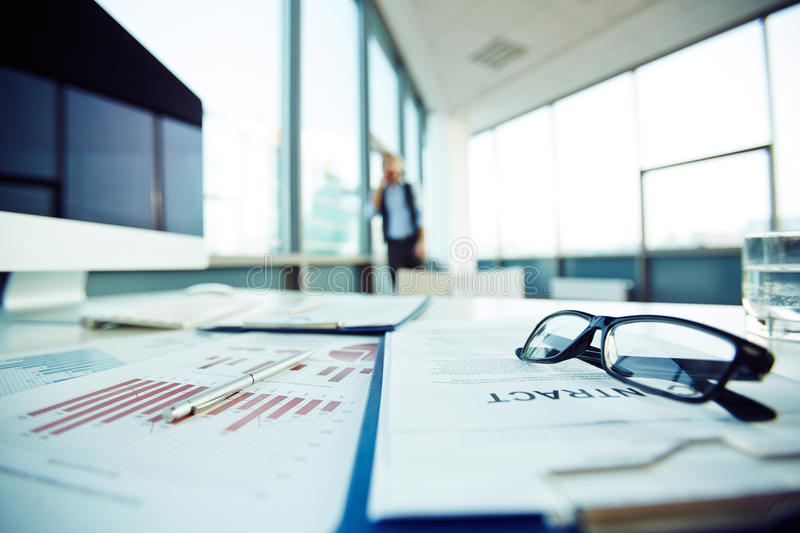 Papers on workplace. Business documents at workplace and employee on background stock photo