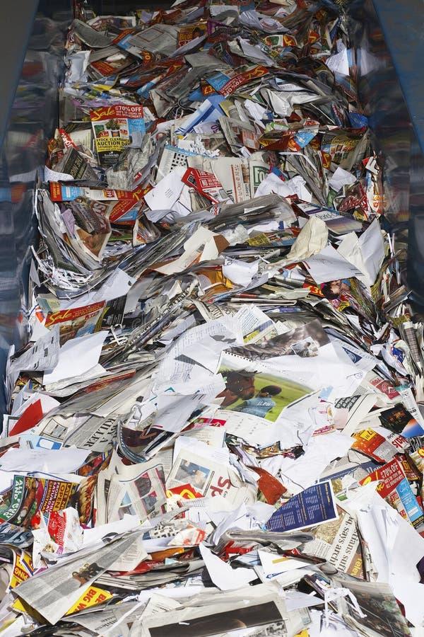 Paperwaste på transportbandet royaltyfria bilder