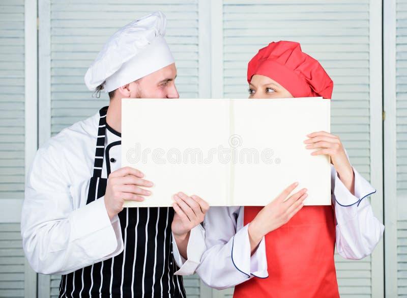 paperwork Шеф-повар и повар приготовления уроков держа пустую счетную книгу Сварите и хелпер выполняя счетоводство Пары человека  стоковая фотография