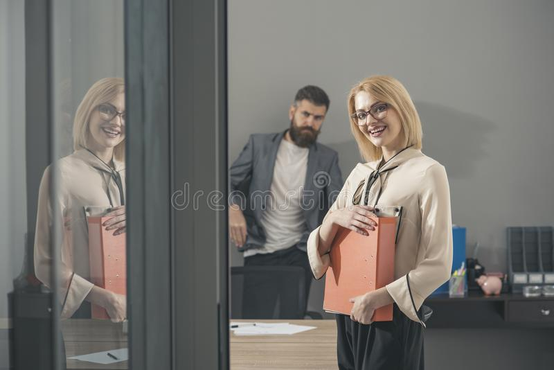 Paperwork before deal. Happy woman and bearded man in office background. Business woman smile with file folders. Paperwork before deal. Happy women and bearded stock images