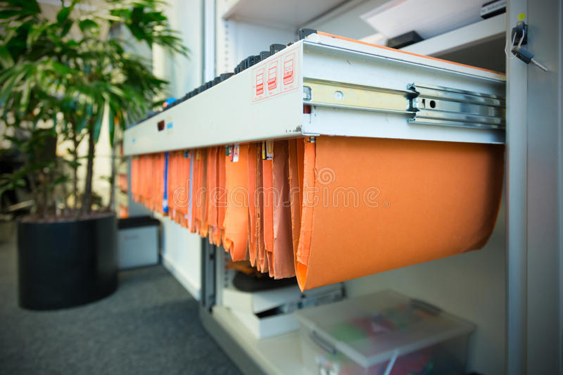 Paperwork in a filing cabinet. Old and used orange paper File Folders in a metal filing cabinet.Cupboard with suspension files stock photography
