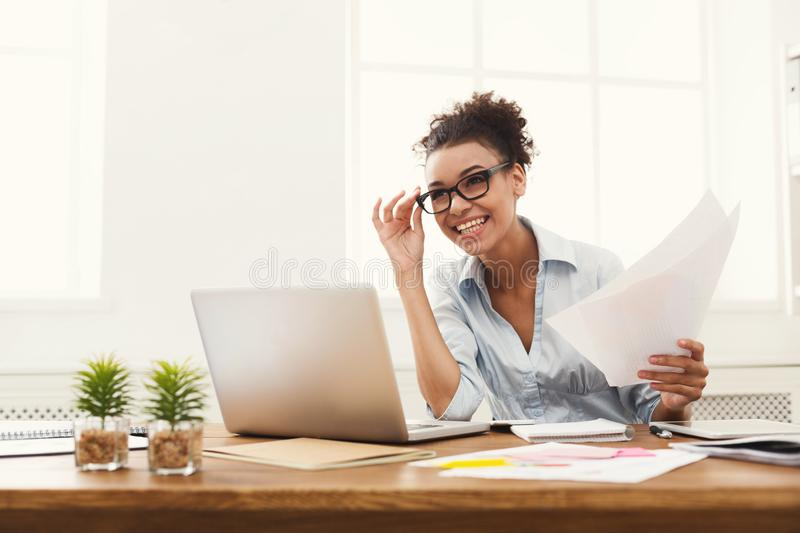 Happy business woman reading document at office desktop stock images