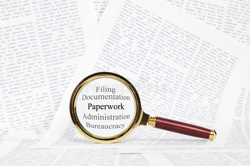 Paperwork and Magnifying Glass Concept. A magnifying glass over the words paperwork, administration, office work, filing,documentation, and paperwork royalty free stock image