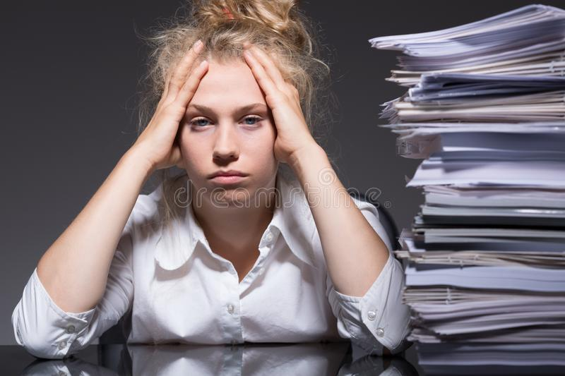 Paperwork in the office. Young woman has lots of paperwork in the office royalty free stock photography