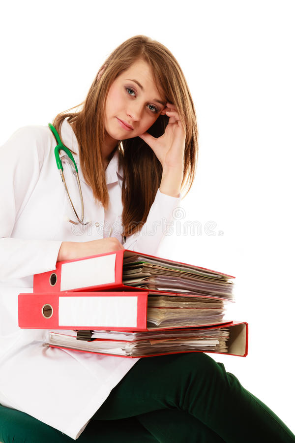 Paperwork. Overworked doctor woman with documents. Medicine and paperwork. Tired overworked busy doctor woman with stack of folders with files documents isolated stock photos