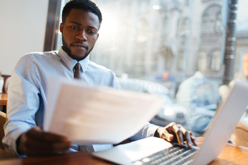 Paperwork. Serious employer reading resumes of candidates for vacancy royalty free stock image
