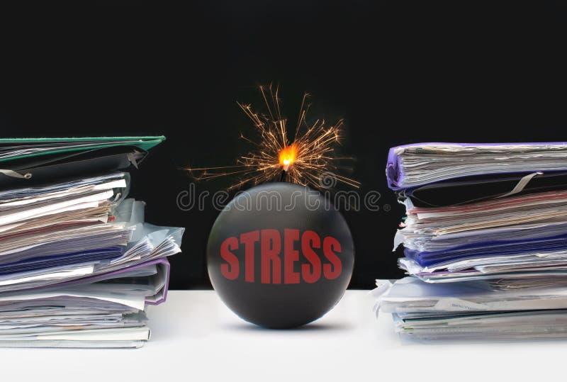 Paperwork stress. Exploding bomb inbetween two stacks of paperwork stock images