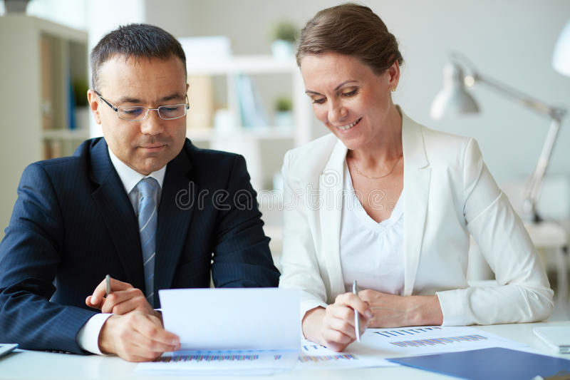 Paperwork. Two mature business partners looking at document in office stock image