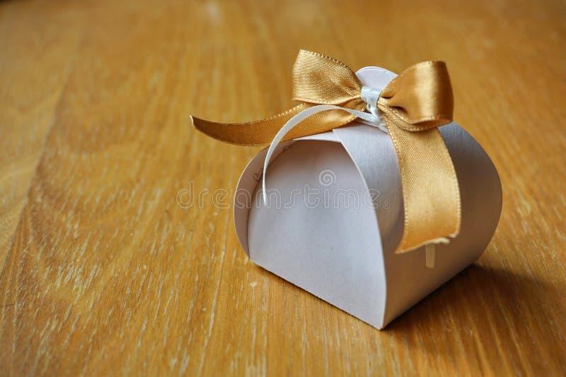 Papery κιβώτιο δώρων με μια χρυσή κορδέλλα στην κορυφή στοκ εικόνα με δικαίωμα ελεύθερης χρήσης