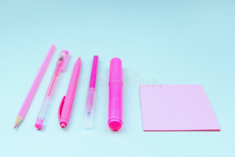 Papeterie au néon rose sur le bureau bleu-clair photos stock