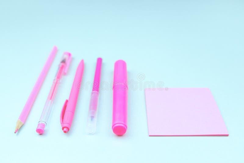 Papeterie au néon rose sur le bureau bleu-clair photos libres de droits