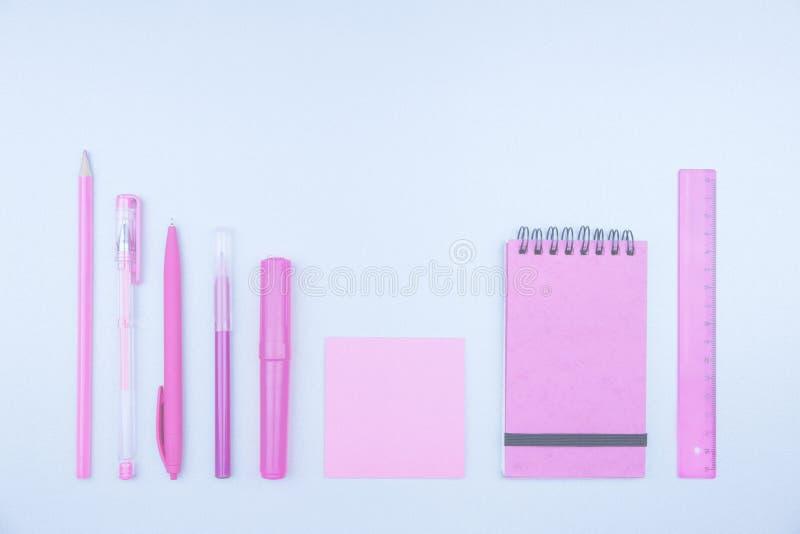 Papeterie au néon rose sur le bureau bleu-clair images stock