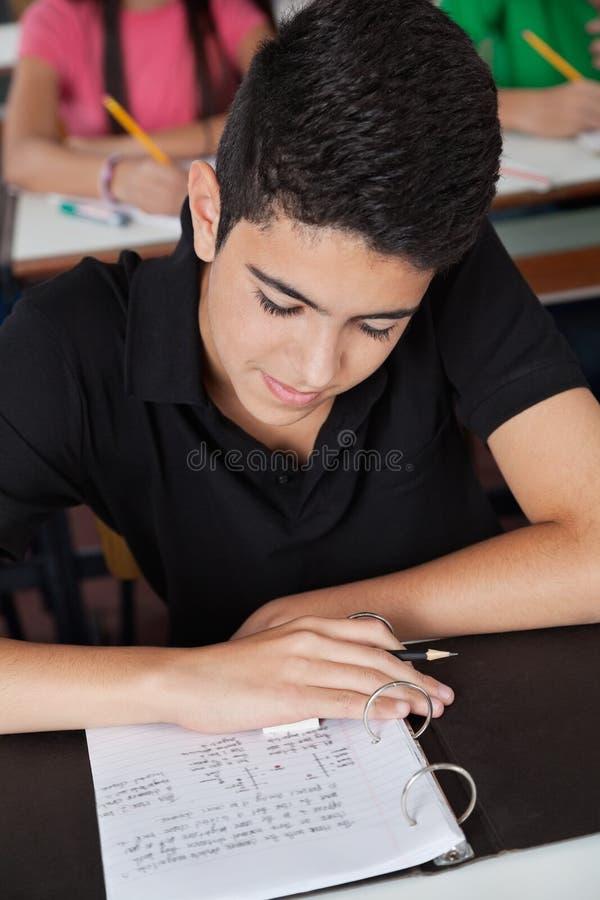 Papier adolescent de lecture d'écolier dans la reliure photos stock