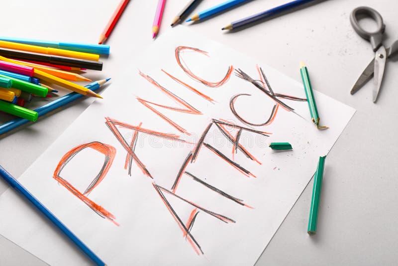 Papier avec l'ATTAQUE de PANIQUE des textes et crayons colorés sur le fond blanc image stock