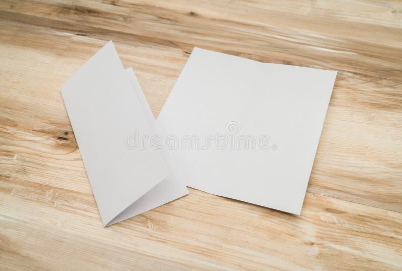 Papier blanc Bifold de calibre sur la texture en bois photo stock