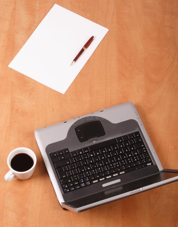 Papier blanc, cuvette de crayon lecteur de café et ordinateur portatif sur le bureau image libre de droits