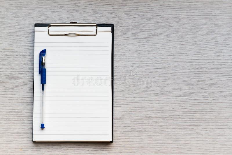 Papier blanc dans le presse-papiers et stylo sur la table en bois photos stock