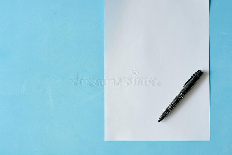 Papier blanc de feuille avec le stylo noir isoleted sur le fond bleu-clair photographie stock