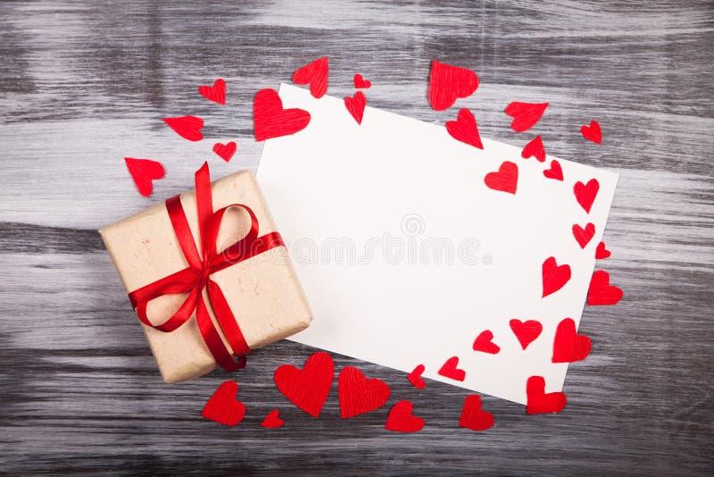 Papier blanc de feuille et un en bois rustique de ruban rouge de cadeau image libre de droits