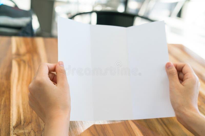 Papier blanc triple de calibre de prise de main de femmes sur la texture en bois image stock