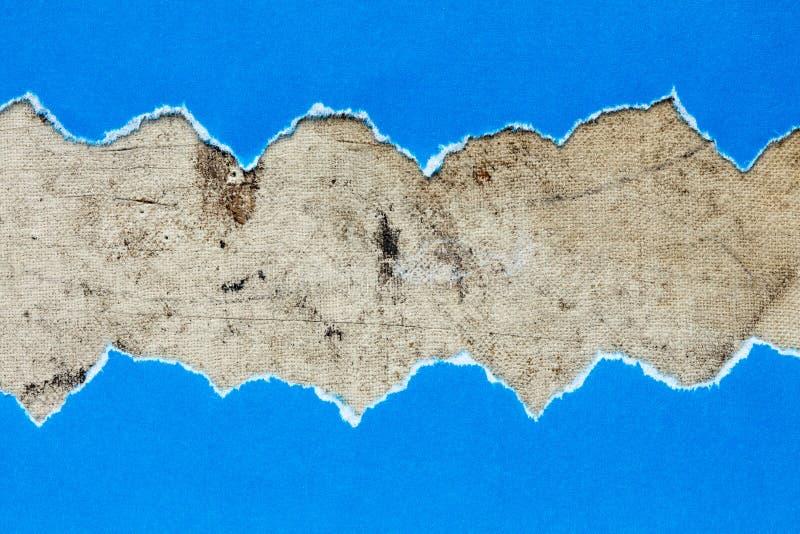 Papier bleu déchiré sur la toile sale photos stock
