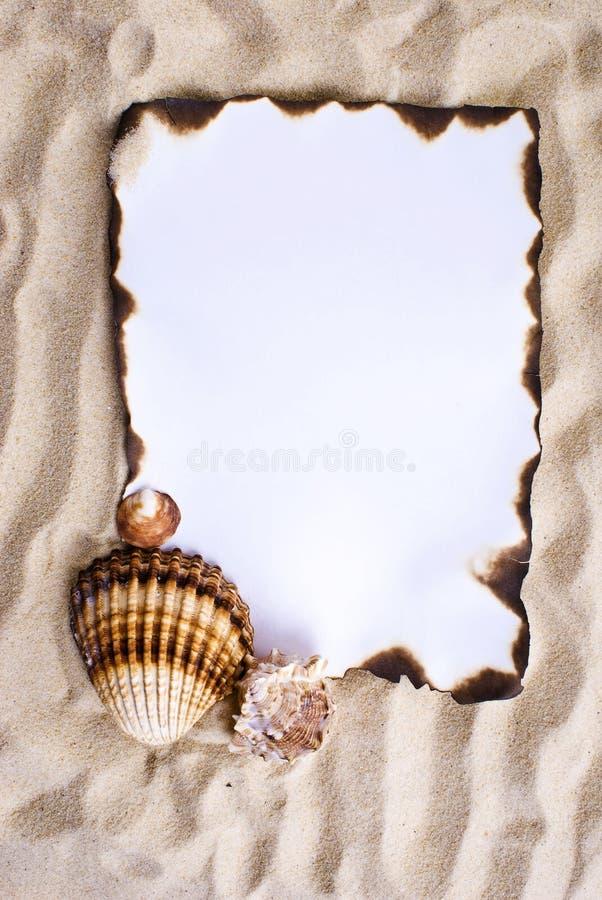 Papier brûlé sur le sable image stock