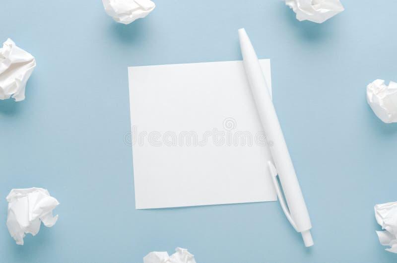 Papier chiffonné blanc et une feuille de papier avec un stylo sur un fond bleu Recherche de concept des idées, inspiration Copiez photographie stock