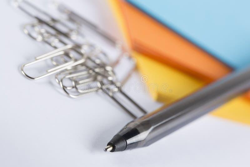 Papier coloré avec des trombones et un stylo photographie stock libre de droits