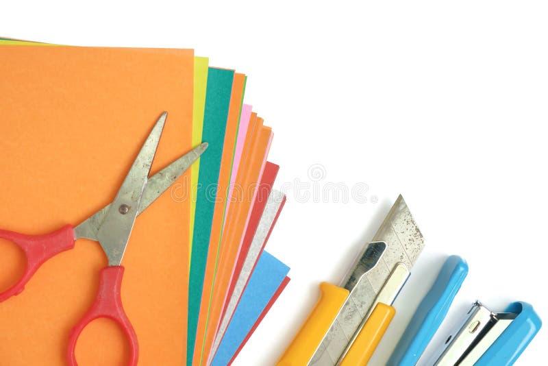 Papier coloré avec le bureau et l'école stationnaires sur le blanc photographie stock