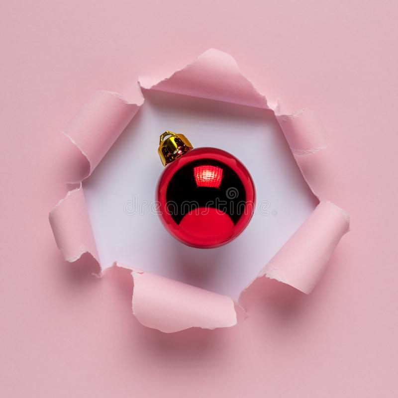 Papier déchiré rose vif avec la babiole rouge de Noël photo stock