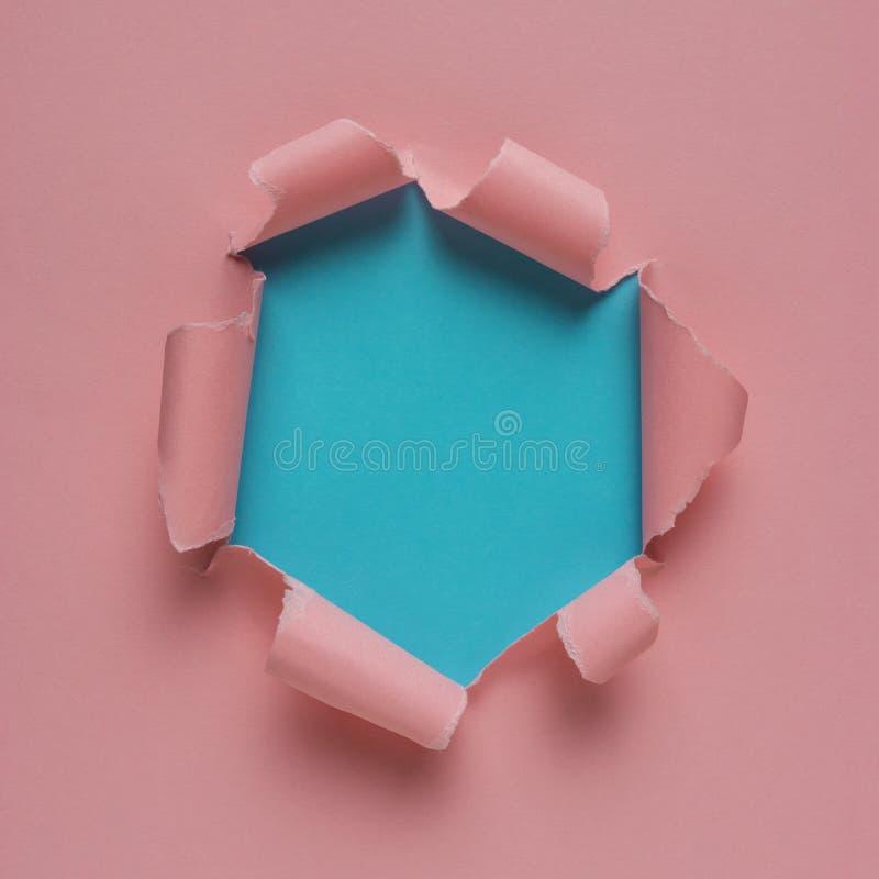 Papier déchiré rose vif avec le fond éclaté de trou photos stock