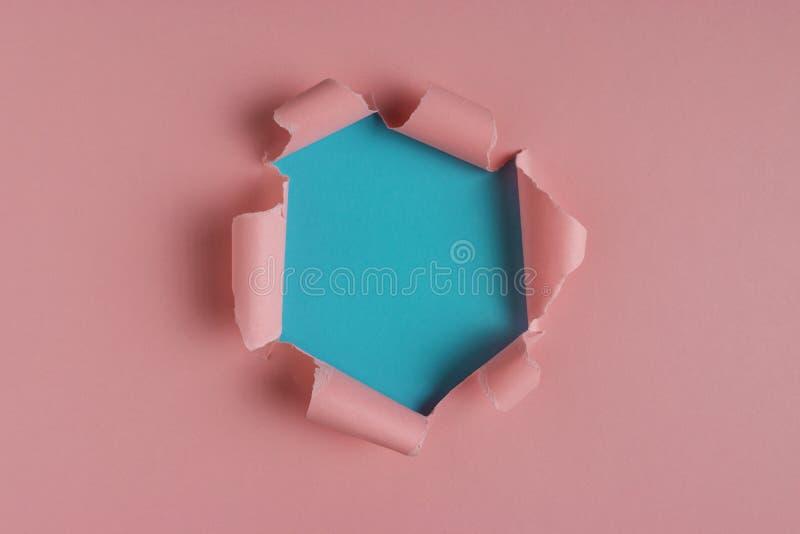 Papier déchiré rose vif avec le fond éclaté de trou E images stock
