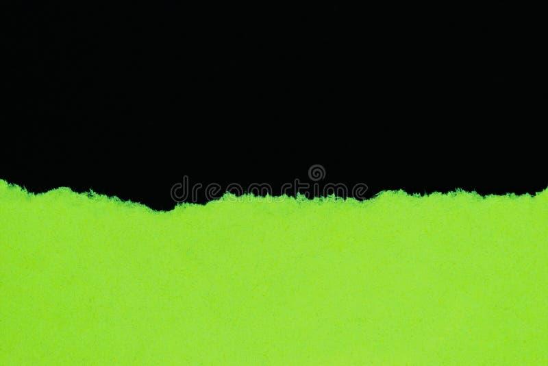 Papier déchiré vert d'isolement sur le fond noir avec l'espace de copie images stock