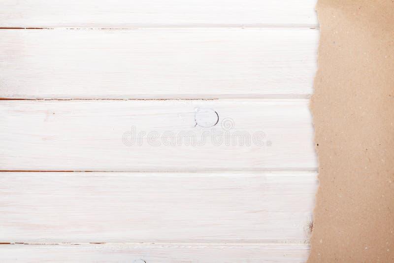 Papier de carton au-dessus du fond en bois blanc photos stock
