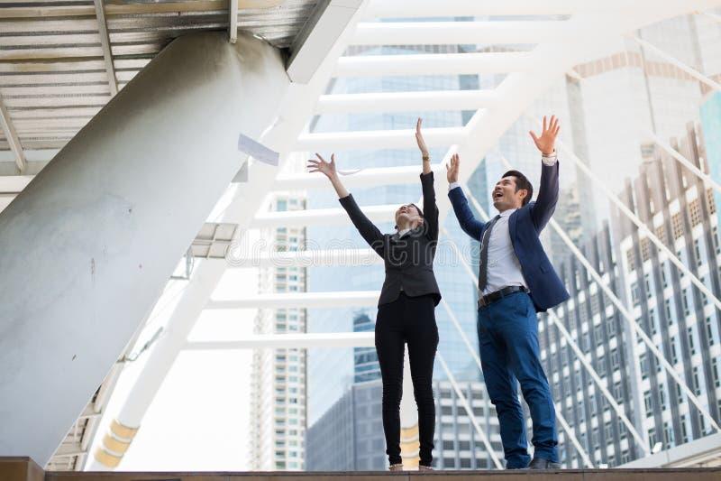 Papier de lancement asiatique d'homme d'affaires et de femme d'affaires à l'air et à soulever deux mains à célébrer pour des affa photos stock